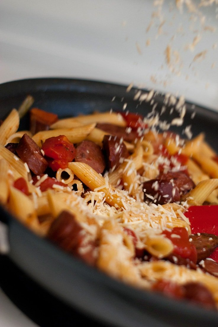 Pouring delicious parmesan cheese onto Penne With Smoked Sausage and Caramelized Onions in a skillet.