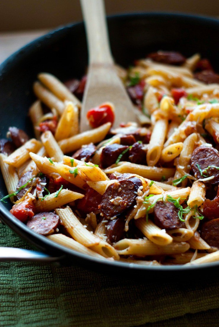Easy Penne With Smoked Sausage and Caramelized Onions in a skillet with a wooden spoon.