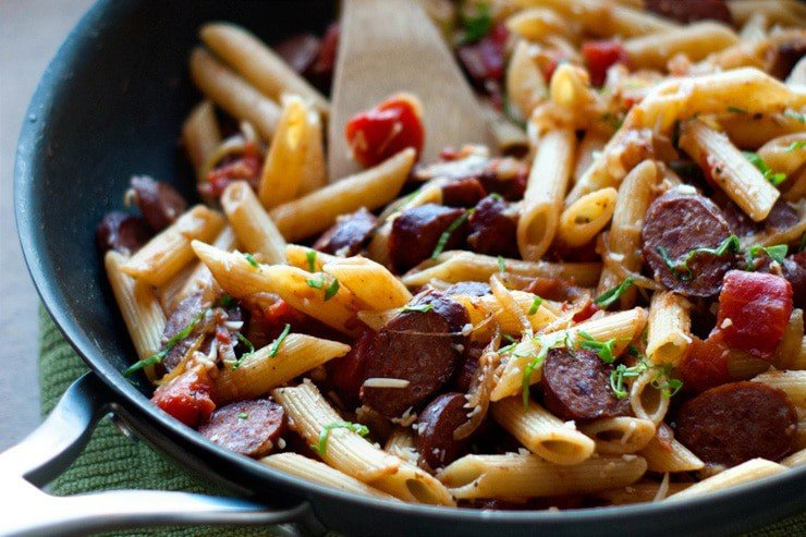 Delicious Penne With Smoked Sausage and Caramelized Onions in a black skillet.