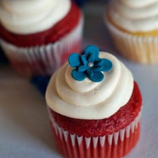 Two simple Red Velvet Cupcakes with delicious cream cheese frosting and a blue flower on top.