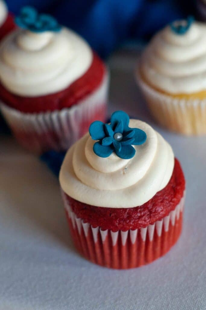 Two Easy Red Velvet Cupcakes with cream cheese frosting and a blue decorative flower on top.