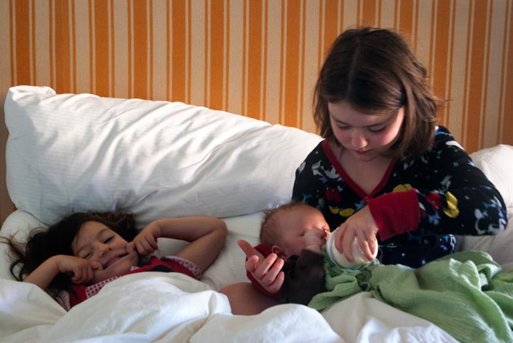 Two young girls feeding bottle to baby in bed.