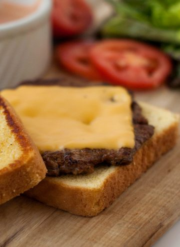 Texas Toast Griddle Burger patty on buttered bread on a wooden board.