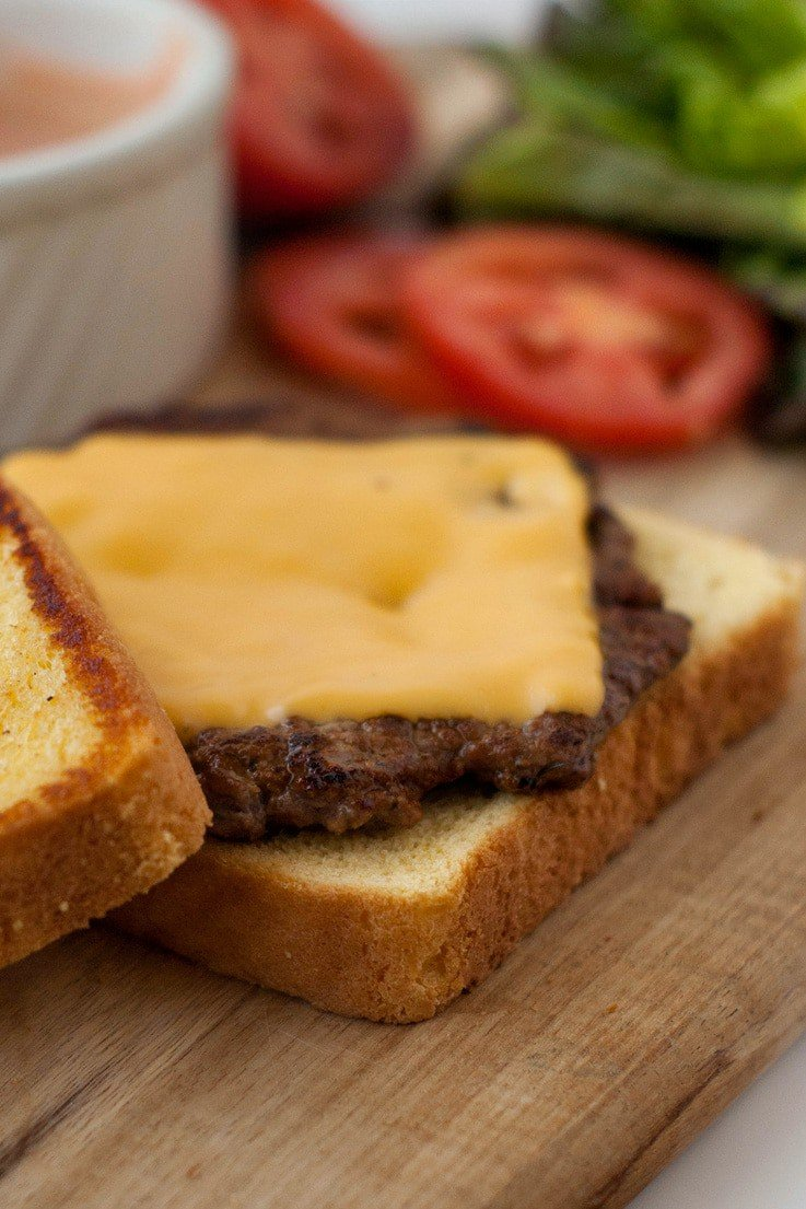 Burger patty with yellow cheese on toasted buttered bread on a wooden board.