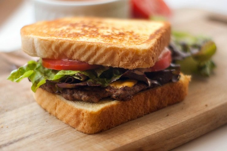 Easy Texas Toast Griddle Burger with tomatoes and lettuce on a wooden board.