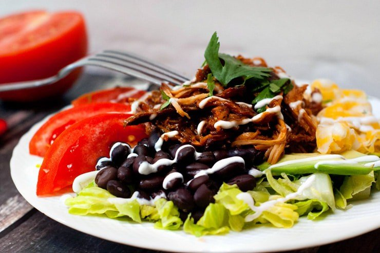 Delicious Slow Cooker BBQ Chicken Taco Salad with black beans and tomatoes.