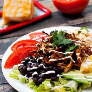 Simple Slow Cooker BBQ Chicken Taco Salad with cheese, black beans and tomatoes on a white plate.