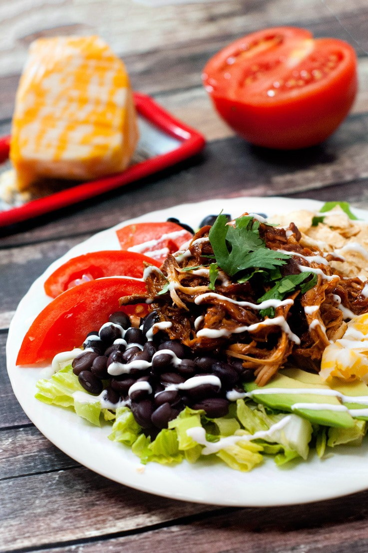 Easy crock pot BBQ Chicken Taco Salad with fresh tomatoes and black beans on a white serving plate.