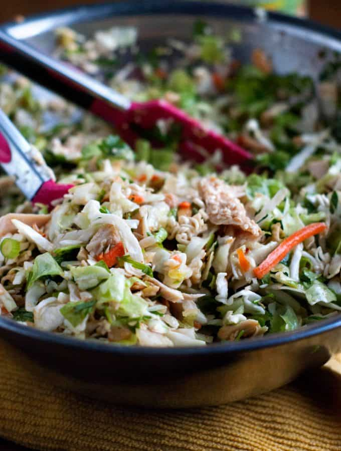 Easy Asian Chicken Salad in a large mixing bowl with pink and silver tongs.