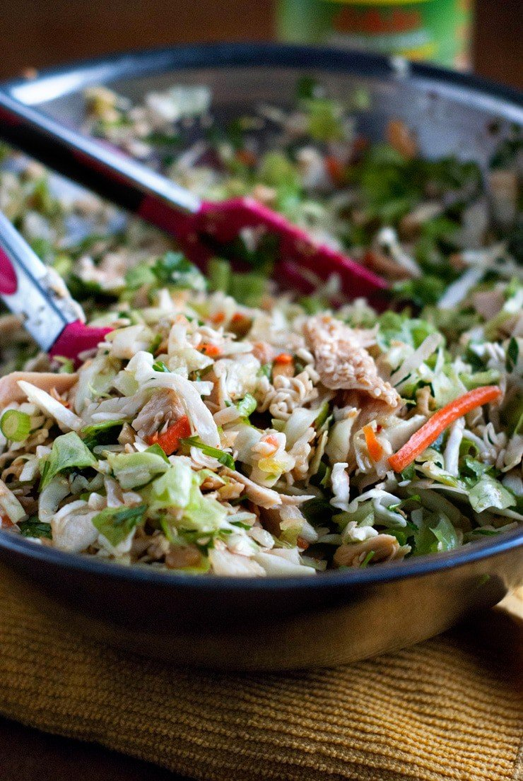 Delicious Asian Chicken Salad with pink and silver tongs in a large mixing bowl.