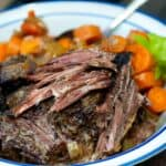 Classic Slow Cooker Pot Roast with carrots, onions and celery on a blue and white plate.