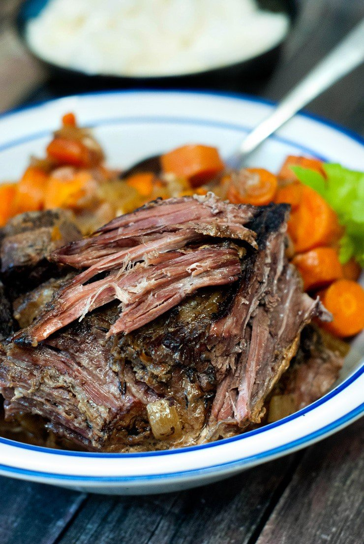 Shredded Crock Pot Pot Roast with healthy veggies on a white and blue plate on a wooden table.