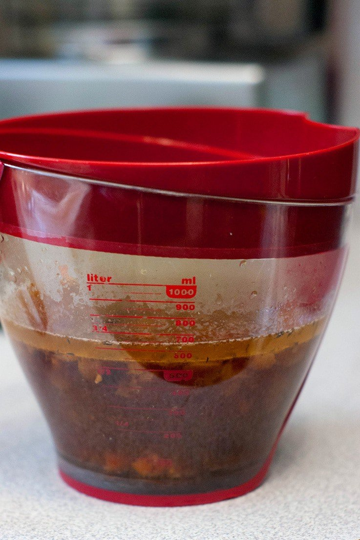 Slow Cooker Pot Roast Gravy on a measuring cup with a red lid.