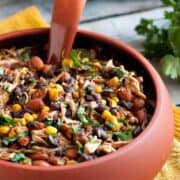 Large red bowl of delicious Slow Cooker Salsa Chicken Chili with corn and beans.