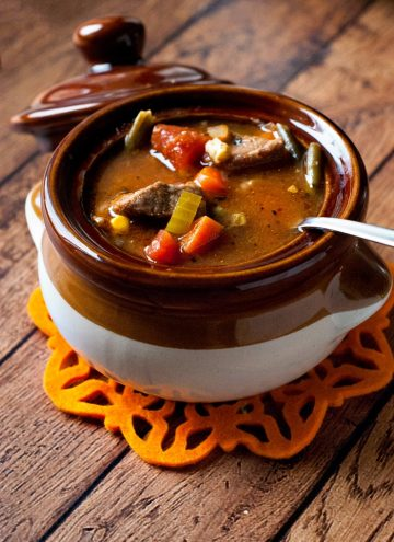 Delicious Slow Cooker Vegetable Beef Soup in a smalll white and brown bowl on a wooden table.