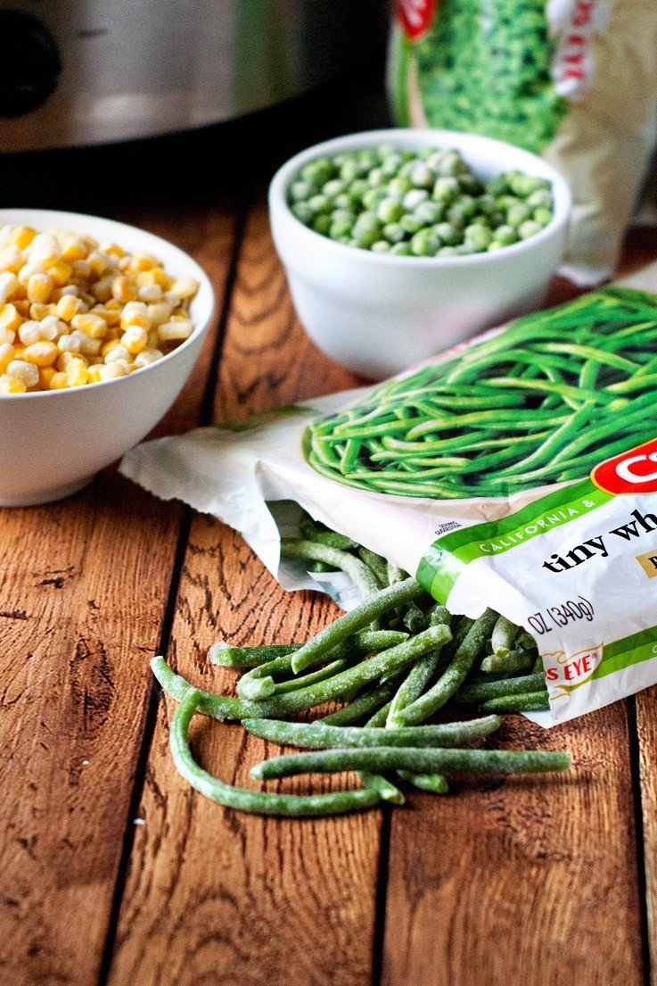 Frozen green beans in a bag, frozen peas in a white bowl and frozen corn in a white bowl on a wooden table.