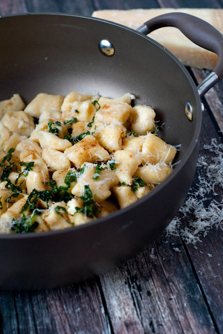 Easy Ricotta Gnocchi on a black skillet on a wooden table.