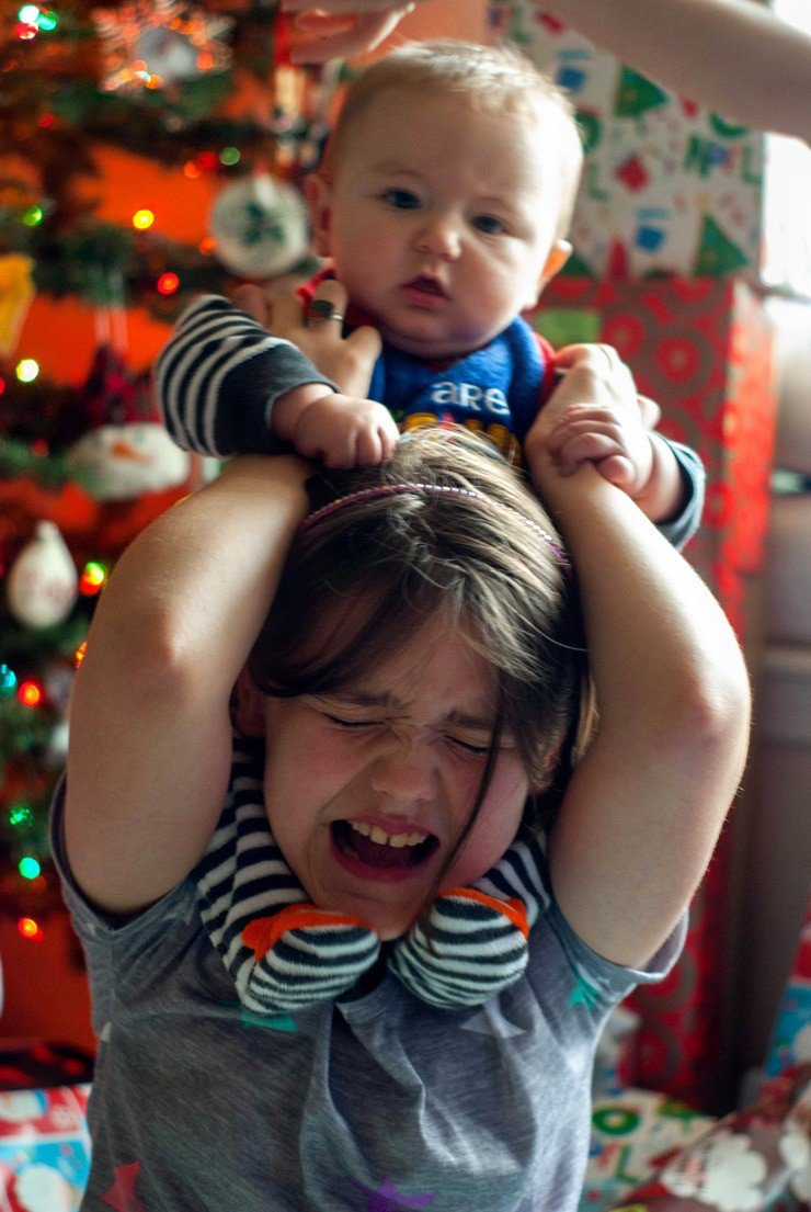 Baby on little girls shoulders on Christmas.