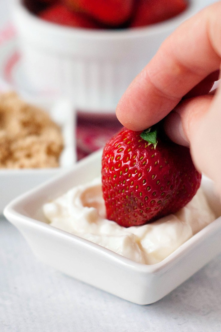 Strawberry being dipped in sour cream