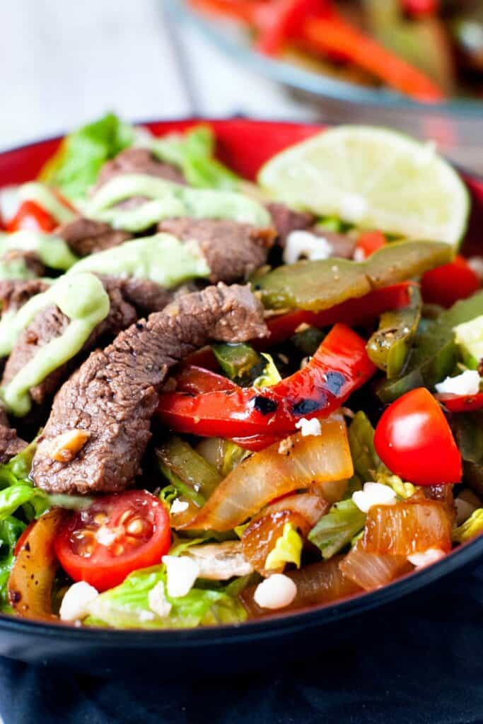 Skillet Steak Fajita Salad in red bowl with slice of lime
