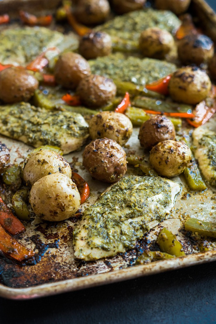 Sheet Pan Pesto Chicken and Veggies-- it only takes one pan for this sheet pan supper! Chicken breasts, mini potatoes and bell peppers are topped with basil pesto and baked! So good and so, so easy! No dishes and No mess!