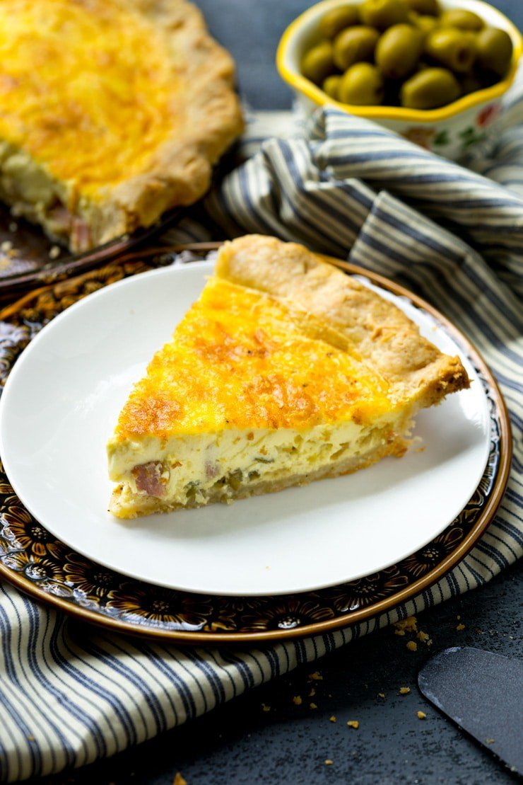 A piece of the best basic quiche recipe on a white plate