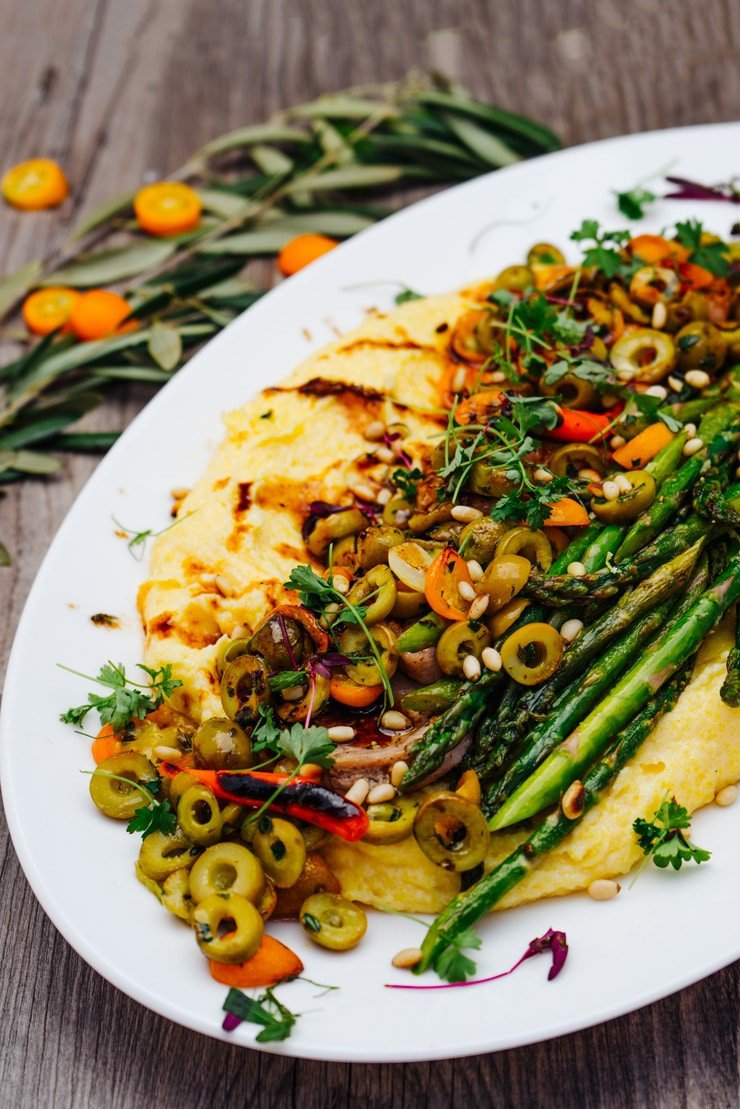 Polenta topped with olives and asparagus