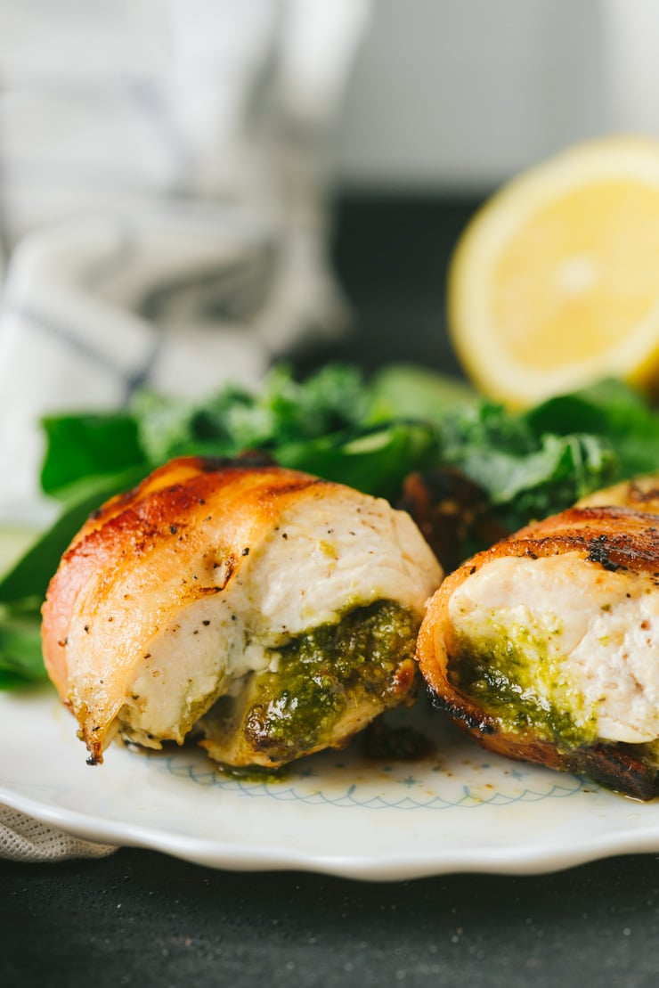 Bacon Wrapped pesto chicken on a white plate