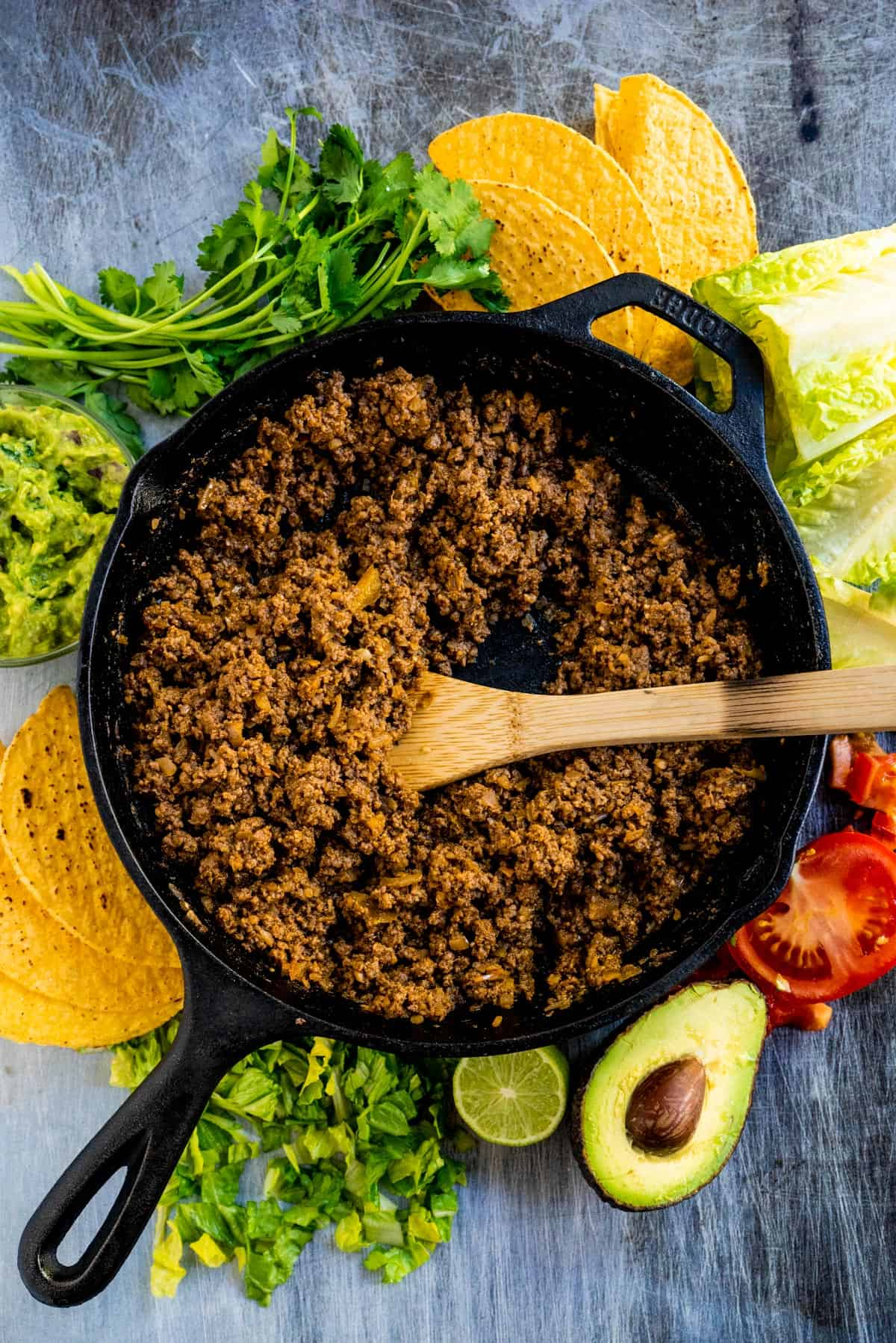 Taco meat in a skillet with toppings all around