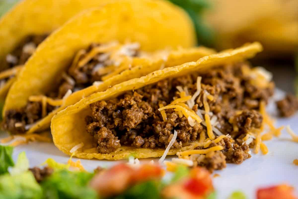 Crunchy tacos with meat and cheese on their sides