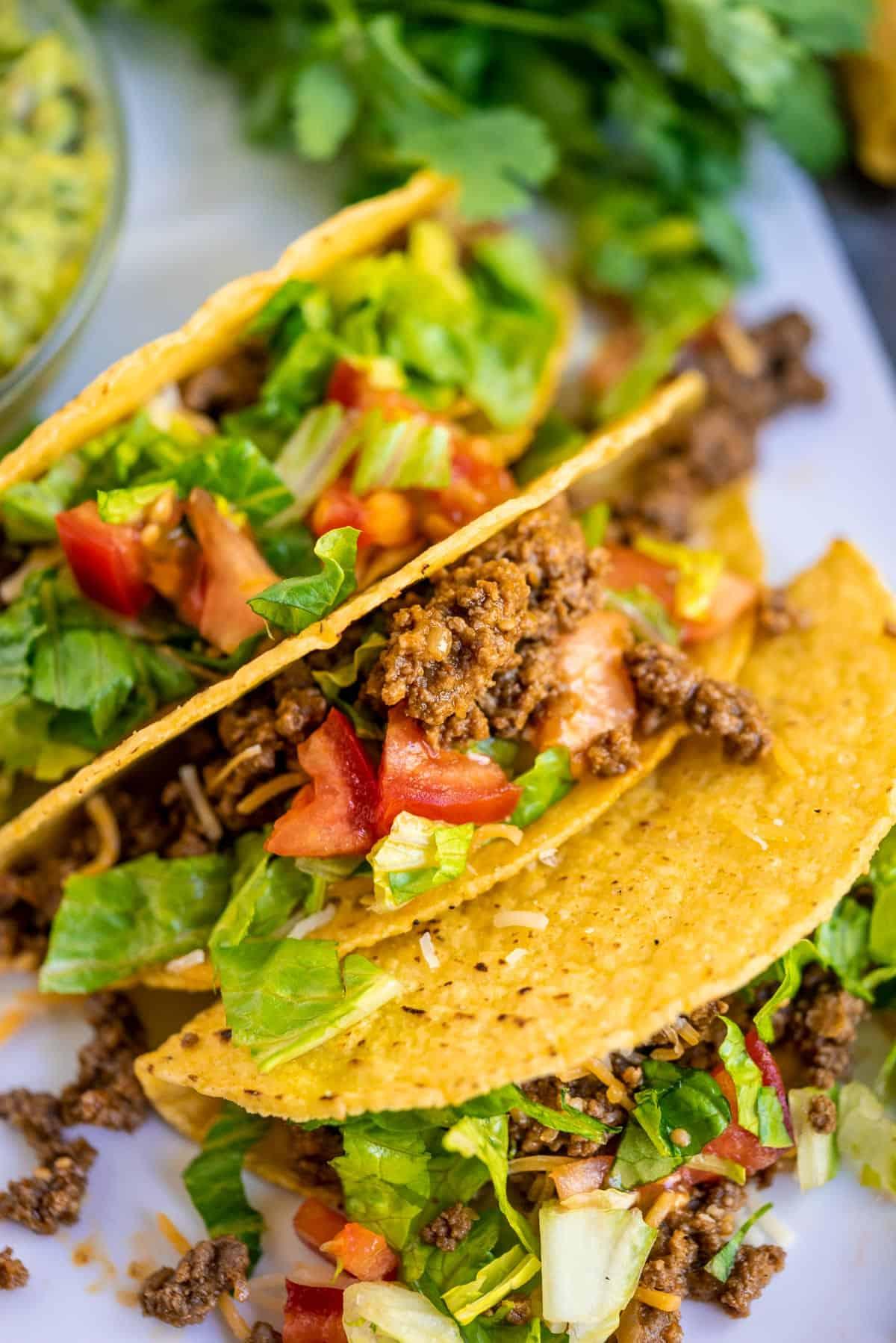 3 crunchy tacos on white platter