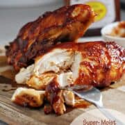 BBQ chicken cut on a cutting board with a bottle of bbq sauce