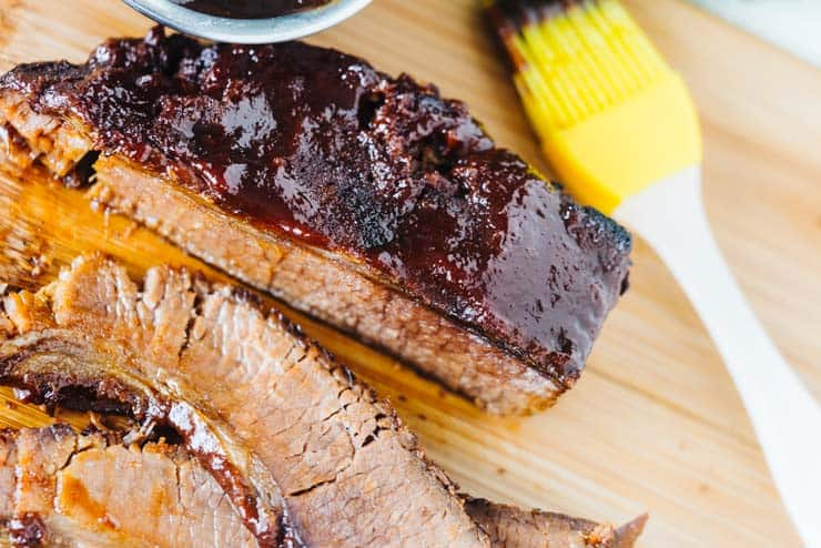 Sliced pressure cooker brisket on cutting board with yellow silicone basting brush