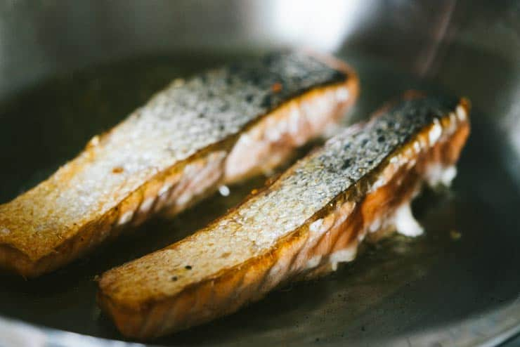 Salmon skin side up in pan