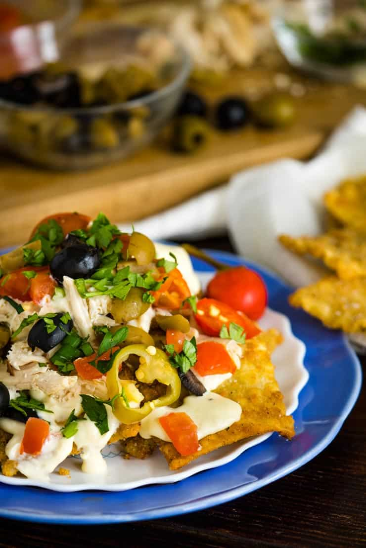 Italian Nachos on a blue plate with alfredo sauce, olives and cherry peppers.