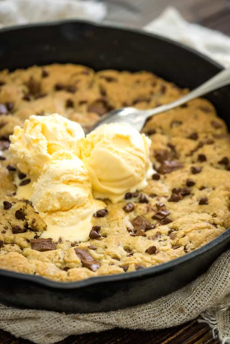 Pizookie recipe in a cast iron pan with vanilla ice cream on top