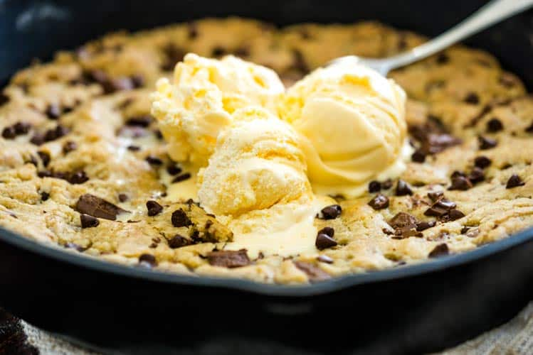 Easy Skillet Cookie baked in a cast iron pan with vanilla ice cream on top.