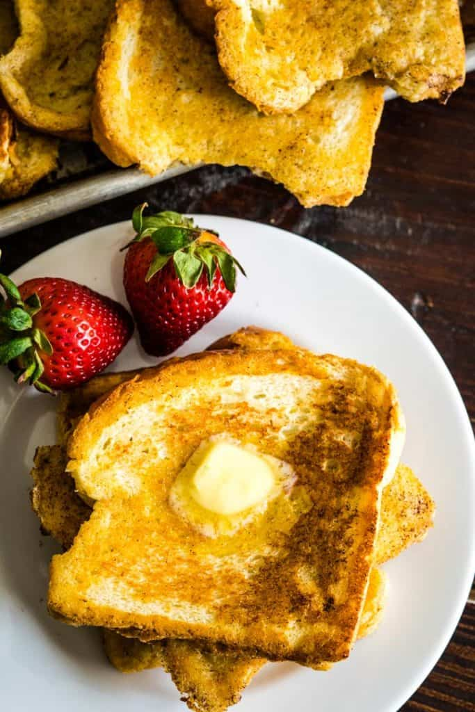 cinnamon french toast on a plate with butter and strawberries