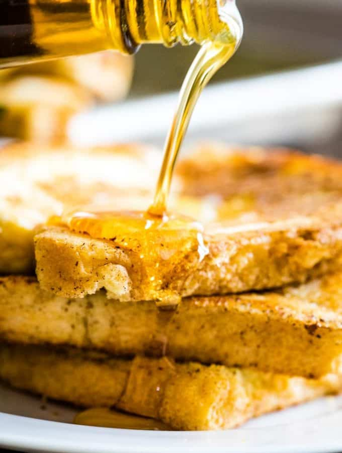 Maple syrup being poured over a stack of easy french toast