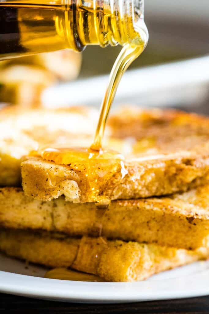 Maple syrup being poured over 3 slices of baked french toast