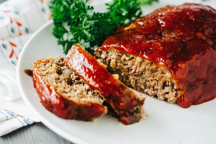 Sliced meatloaf on a white plate with ketchup glaze