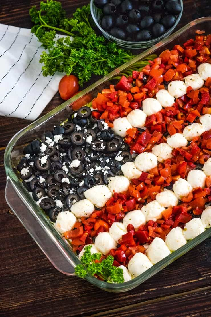 Fourth of July Dip Decorated like a flag with tomatoes, peppers, mozzarella and black olives.
