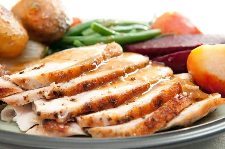 sliced turkey with gravy and vegetables on plate