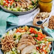 Chinese Chicken Salad in 2 grey bowls on a white table cloth and turquoise napkins