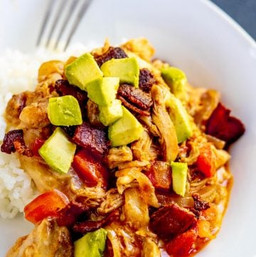 Saucy chicken over rice topped with avocado, bacon and tomato on a white plate with a fork