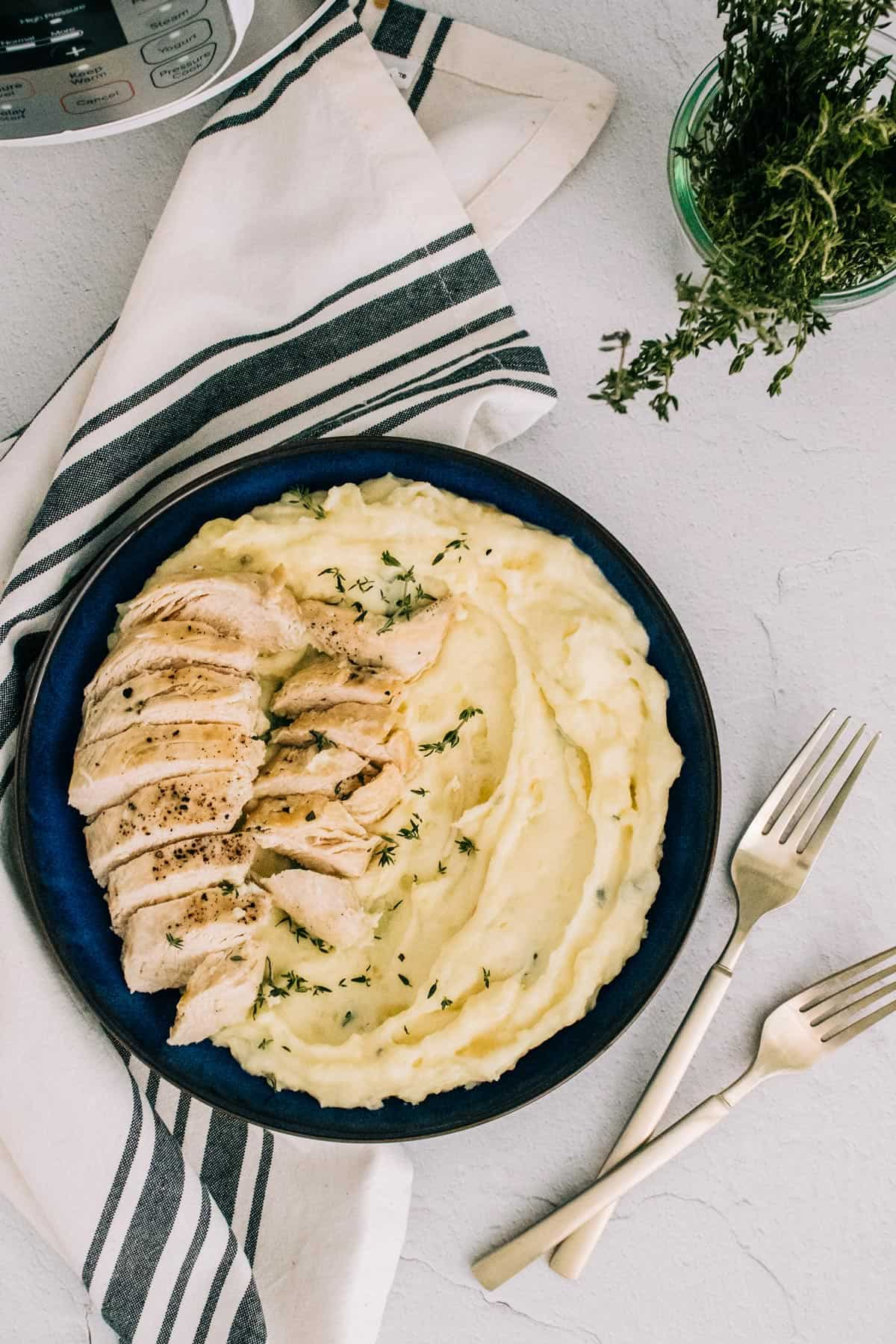 Mashed potatoes and sliced garlic butter chicken on a blue plate
