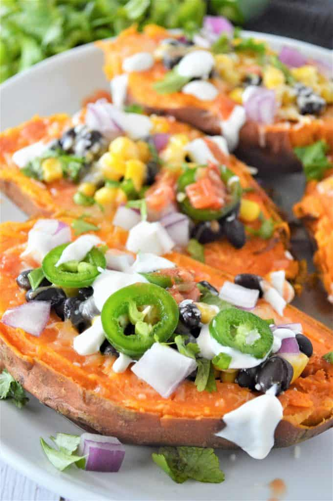 3 sweet potatoes on a plate stuffed with toppings