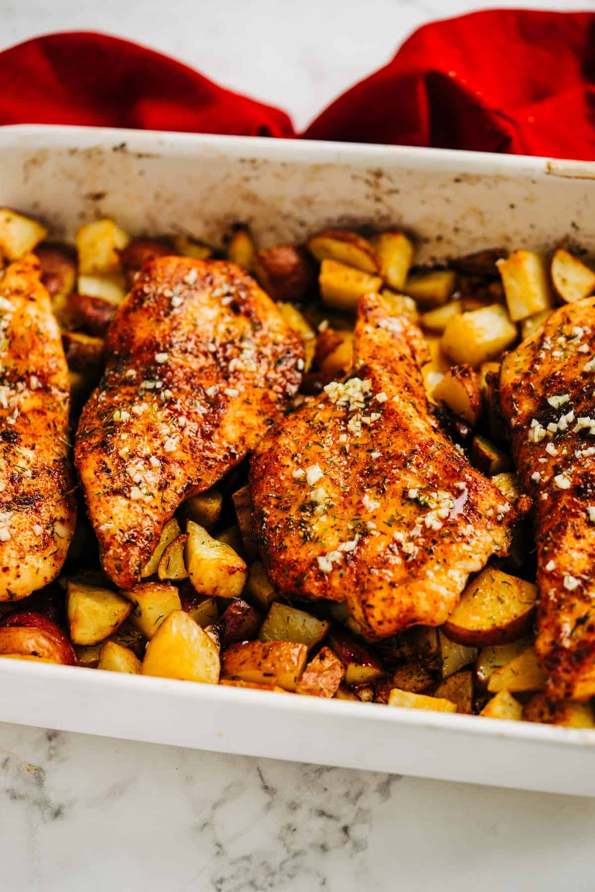 4 seasoned chicken breasts in a pan with potatoes