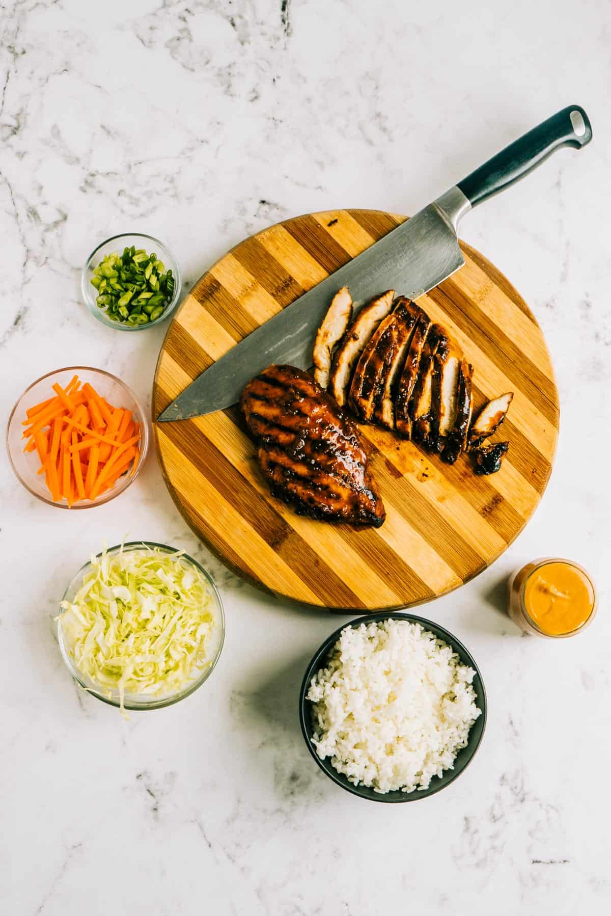 Overhead view of grilled chicken on a cutting board and rice bowl ingredients