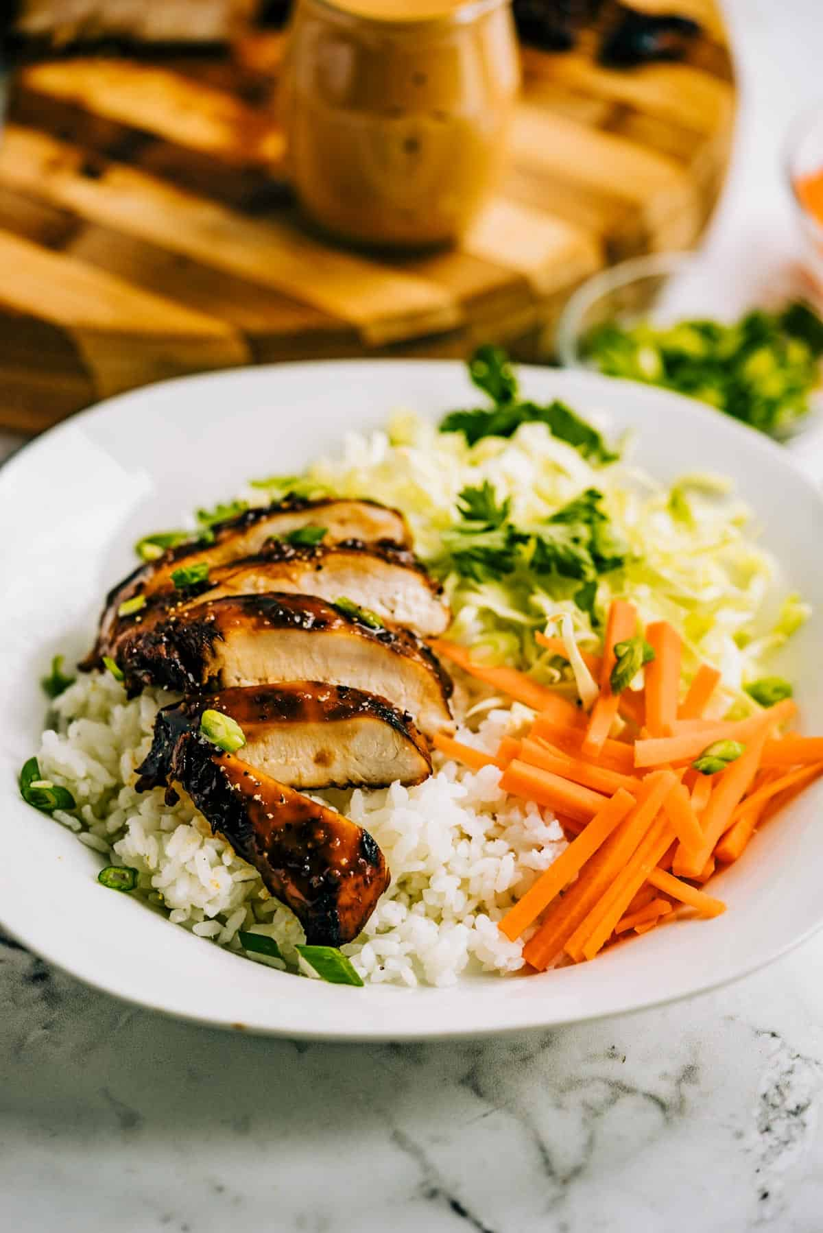 Grilled chicken on rice with carrots, celery and cilantro